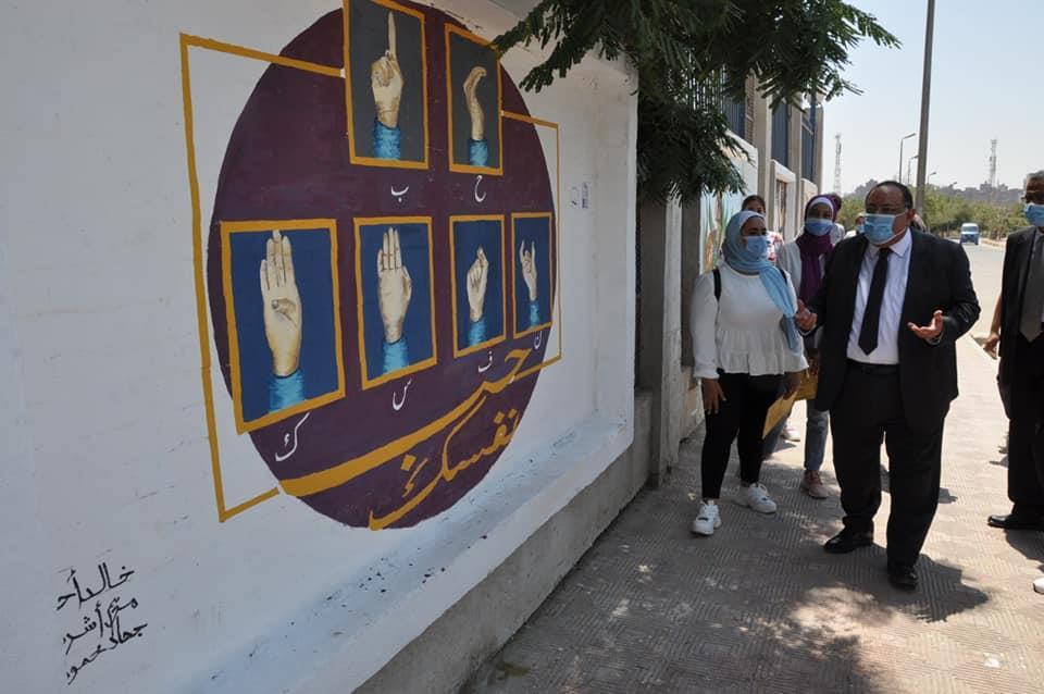 تجميل سور جامعة حلوان بلوحات إبداعية بأيدي طلاب كلية التربية الفنية ورئيس الجامعة يكرمهم.