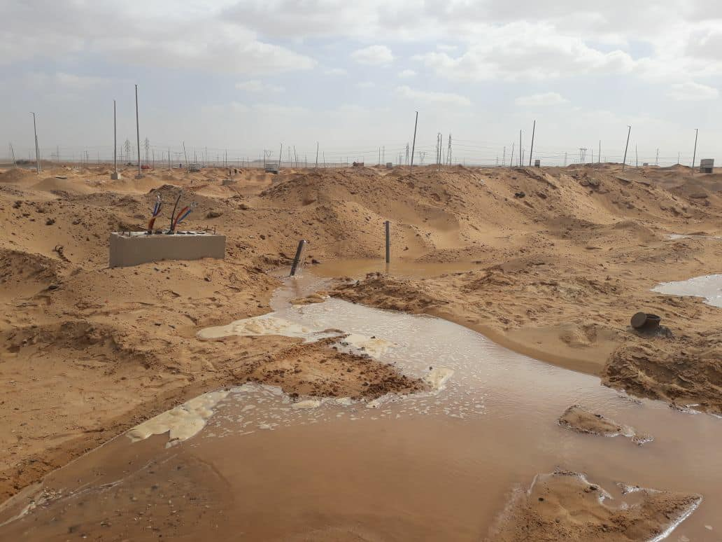 صورة توضح إزاحة الرمال ورشها بالماء