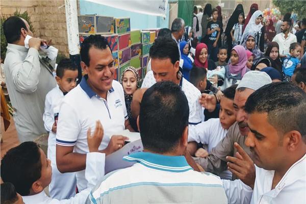 مينا أثناء توزيعه الهدايا