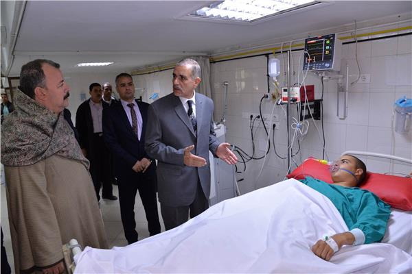 محافظ أسيوط اللواء جمال نور الدين مع أحد المصابين