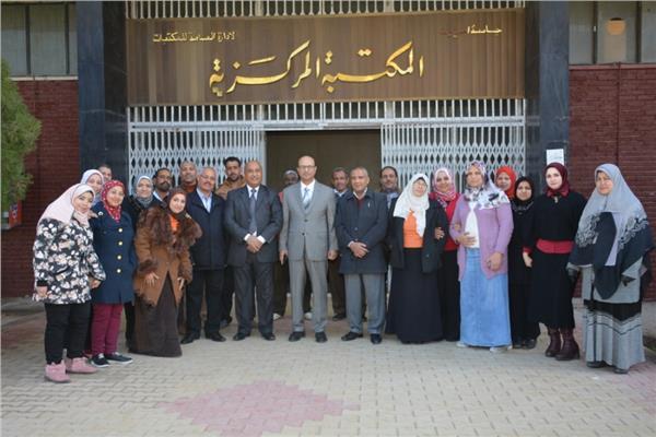 المنشاوي مع العاملين بالمكتبة والطلاب بجامعة أسيوط