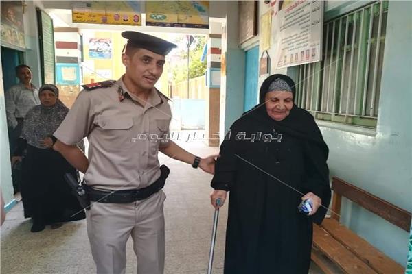 شرطى يساعد عجوز بإحدى لجان سوهاج