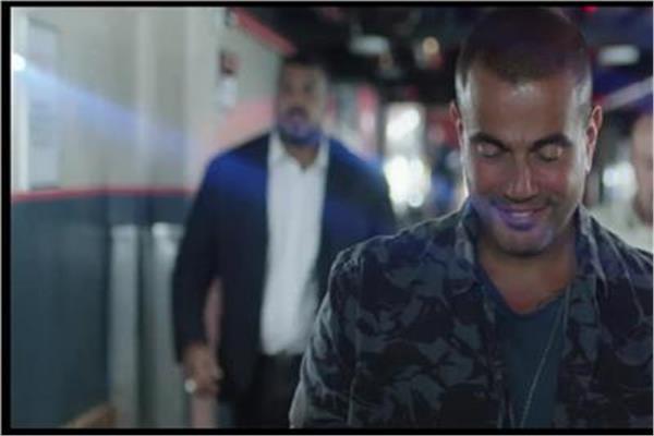 تايسون خلف المطرب عمرو دياب خلال الإعلان