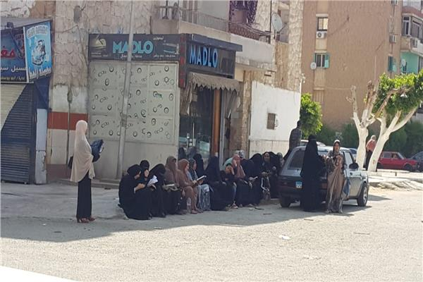 امهات الطلاب والطالبات تركن محيط اللجان وتولين الى ظل لقراءة القرآن