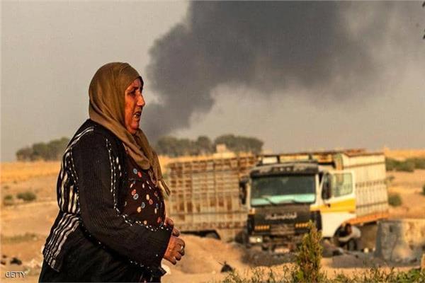 سيدة سورية تهرب من القصف التركي