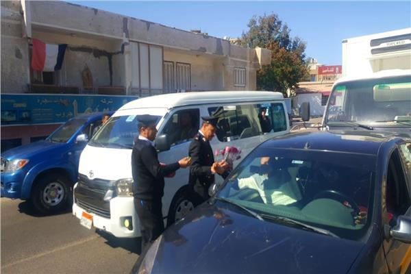 رجال الشرطة يوزعون الورود والحلوى على المواطنين بشوارع الغردقة
