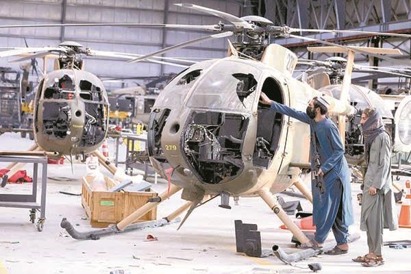 مقاتلان من طالبان يتفقدان كابينة قيادة مروحية أفغانية