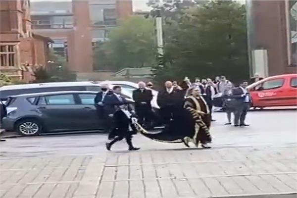 هيلاري كلينتون اثناء توجهها للمبني الجامعي و طفلة تحمل لها زيل المعطف