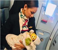 صورة  مضيفة ترضع طفلاً على متن طائرة