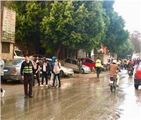 رغم برودة الجو.. رجال المروريقفون تحت الأمطار لتسيير حركة الشارع
