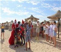 بابا نويل يوزع الهدايا والورود على السائحين بشواطئ مرسى علم | صور