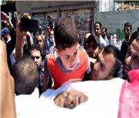 نجل الصحفي الفلسطيني الشهيد فى غزة يلقي نظرة الوداع على جثمان أبيه