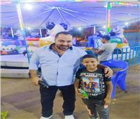 مرقص شاب قبطي يوزع الهدايا والألعاب على الأطفال في شوارع بني سويف
