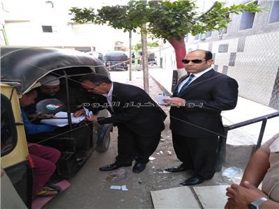 المستشار ياسر جمال خلال مساعدة المريض على الإدلاء بصوته