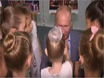 الرئيس الروسى بوتين يجلس على ركبتيه ليقبل يد طفلة صغيرة
