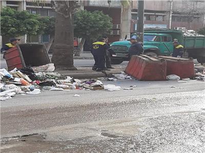 عمال نظافة وهم يقومون برفع القمامة