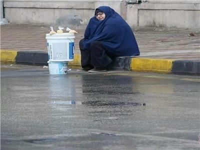 سيدة مسنه تجلس علي الرصيف في عز المطر