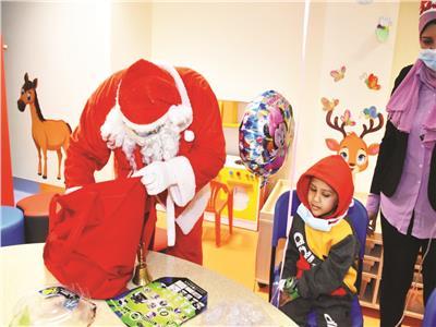 بابا نويل يداعب أطفال الصعيد