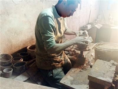 أحد العمال يصنع الفخار