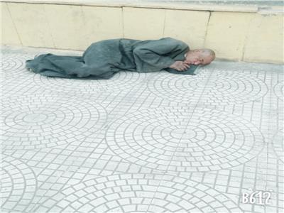 """صورة للشيخ """"علي"""" وهو ينام على رصيف محطة طهطا"""