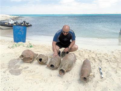 عالم الآثار البحرية خلال فحص بعض الآثار