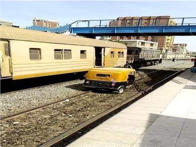 توك توك يسير على قضبان السكة الحديد بجوار القطارات