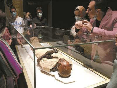 الزائرون يستمعون لشرح حول احدى المومياوات بالمتحف