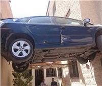 فيديو وصور| سيارة معلقة بالهواء.. كيف استقرت بين الجدارين؟