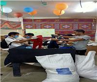 سفير تايلاند و35 طالب بجامعة الأزهر يساعدون فى تجهيز ملابس عيد الأضحى