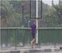 «شورت وفنلة وكوتش».. شاب يتحدى الأمطار بالتريض على كوبري أكتوبر