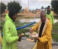 منخفض التنين| صور.. رئيس مدينة برج العرب يوزع الطعام على عمال كسح الأمطار