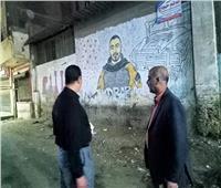 نظافة وتجميل أمام صورة جدارية للشهيد خالد المغربي بطوخ في القليوبية