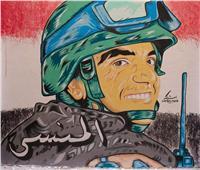 طالب بجامعة أسيوط يرسم لوحة فنية للشهيد أحمد المنسى على أحد الجدران بالقوصية