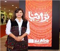 صور| تشجيعا لهم..وزيرة الهجرة ترتدي فستانا من الحرف اليدوية