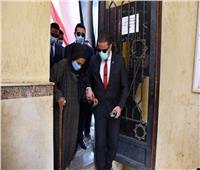 صور  محافظ الفيوم يساعد مسنة في الوصول إلى لجنتها الانتخابية