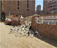 صور| أهالي العشرين بالهرم يعانون من تلال القمامة