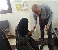 رئيس لجنة انتخابية يساعد مُسنة على الإدلاء بصوتها ببني سويف