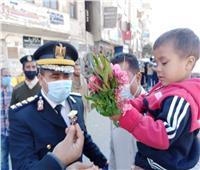 عيد الشرطة| رجال الأمن يوزعون الورود والحلوى على المواطنين بقنا